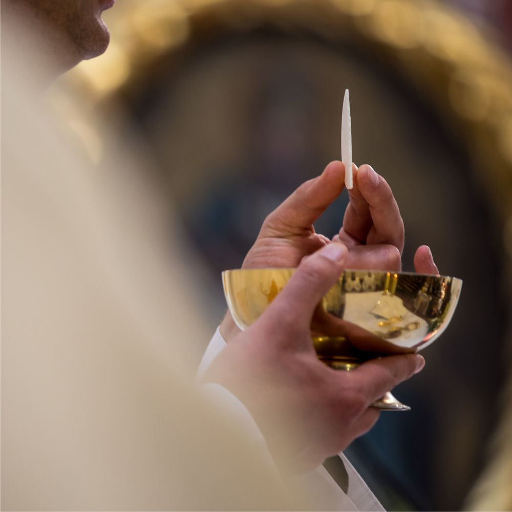 Priest giving communion